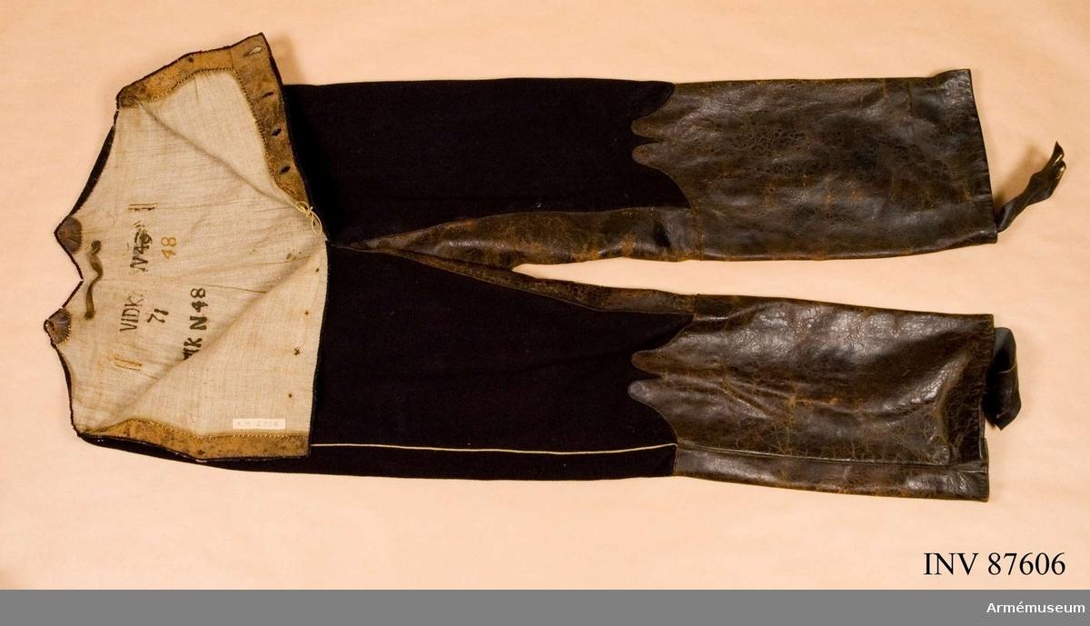Grupp C: I.  Byxor av mörkblått kläde med gul passepoil, stövelskoning och benläder samt fodrade med grått linne. Hällor av läder.