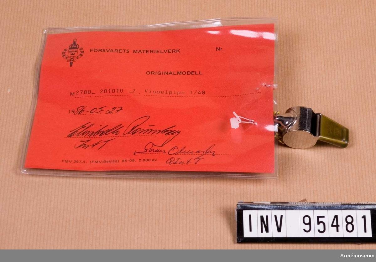 """Vidhängande etikett: """"Försvarets materielverk Originalmodell M 2780-201010-7, Visselpipa T/48, 1986-05-27 (oläslig underskrift)""""."""