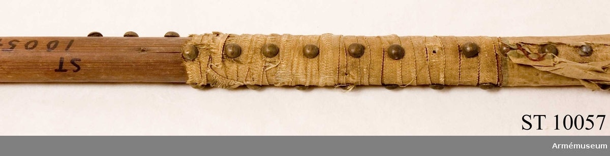 Av barrträ. Fragment av gul sidendamast. Gult tännlikeband och röda trådrester.