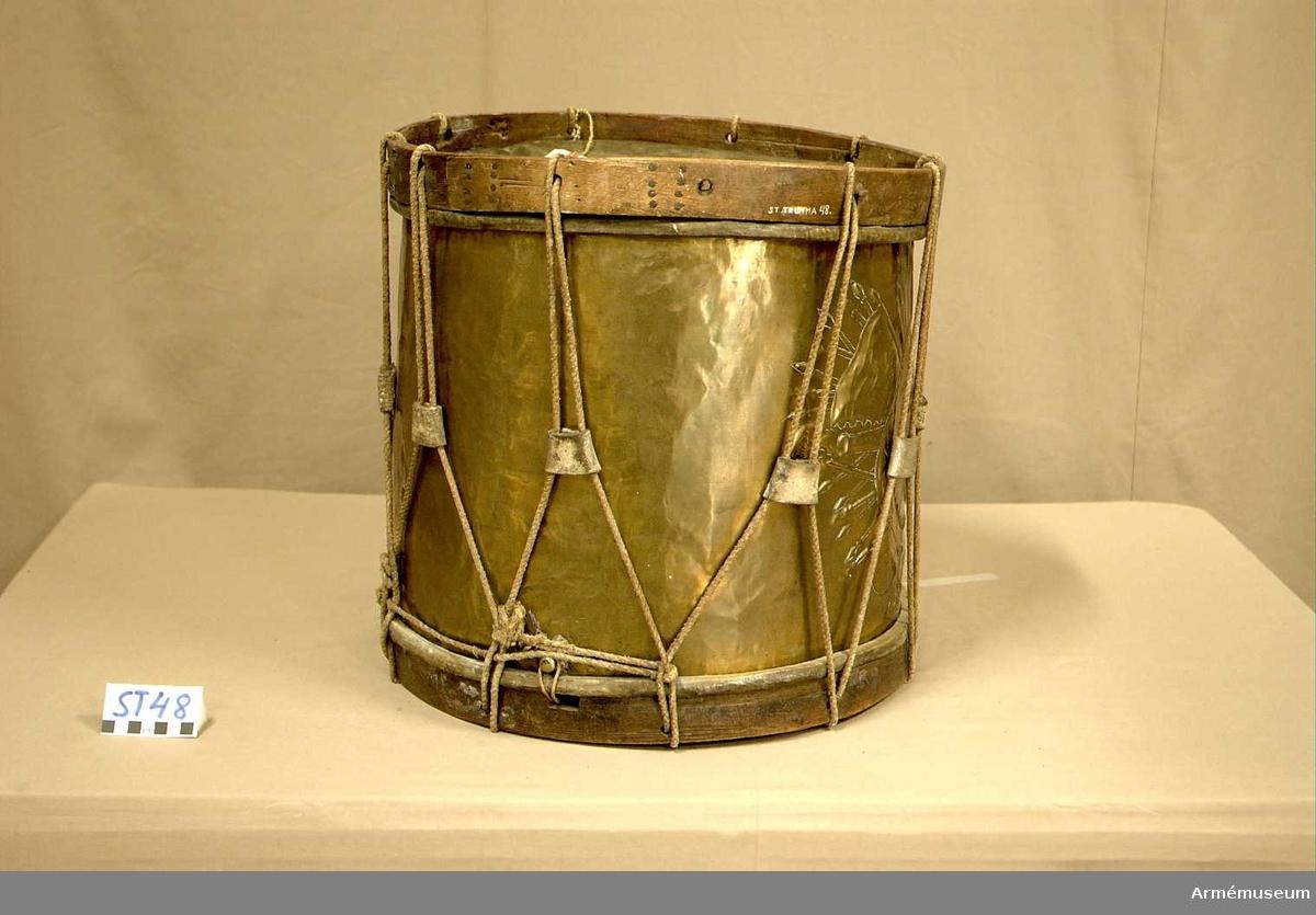 Cylindertrumma av: dekorerad ljus metall. Cylindern har spruckit. Det finns ett flertal mindre lagningar och en större lodrät lödning längst hela cylindern.  Membran : båda trumskinnen är hela, förutom i det undre skinnet, där det finns fem hål i varierande storlek. Från sejarhållaren löper ett tunt rep över det undre skinnet. Skinnen har ett grönaktigt metalliskt utseende.   Spännringar: två par.  Veckelgjordar: är tillverkade i tre delar. Den övre har fyra hål, i par.  Den undre veckelgjorden har en 2 x 1 cm utsågning, här har det spruckit och det saknas en flisa.  Spännlina: är hel. Det finns 9 st. spännstroppar.  Sejarhållare: finns, med ett blomblads dekorerat hål till höger.  Utsmyckning : Vapensköld med bevingat lejon kringgärdat av en mängd vapen.  Märkning : finns.