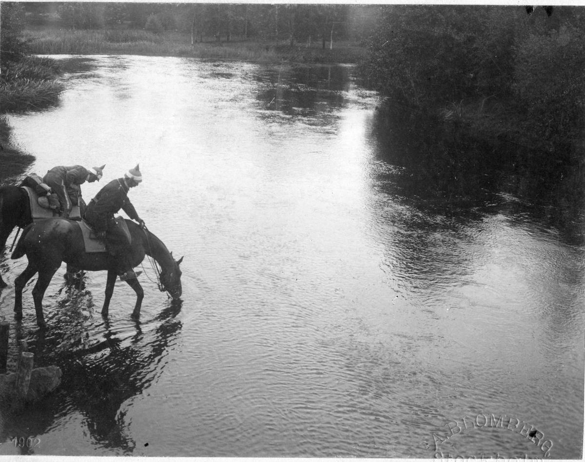 Två ryttare från Livregementet till Häst, K 1,  vattnar sina hästar vid Spångeån.