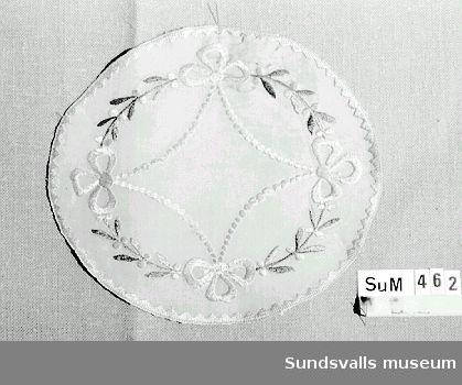 Oval tablett med broderade gula och gröna girlander i plattsöm.