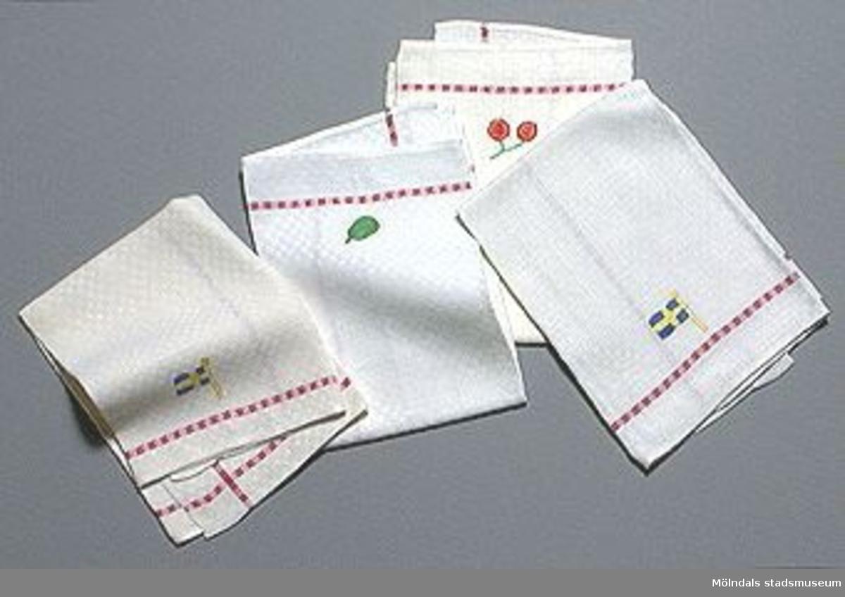 Maskinvävt tyg. Linnehanddukar med smal röd rand en bit innanför kanten. På handdukarna har broderats: två körsbär, en svensk flagga, ett päron, en svensk flagga.