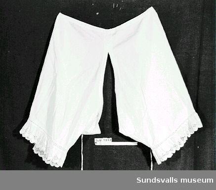 Benkläder av vit bomull med spets på benens kant. På framsidan är namnet 'Ella' broderat i kedjestygn.