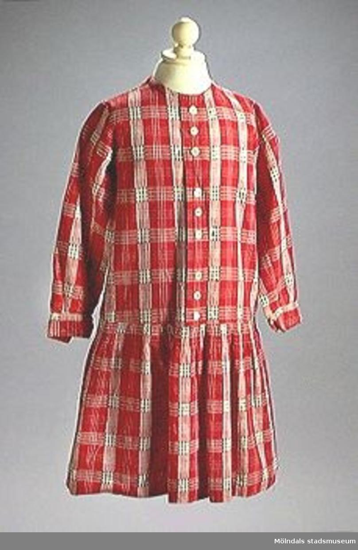 För barn. Röd-vit-rutig med svart i de vita rutorna. Knäppes framtill med tryckknappar. Nio knappar för dekoration på knappslå. Avskuren under midjan med rynkad kjol. Lång ärm. Ryggbredd: 400 mm.