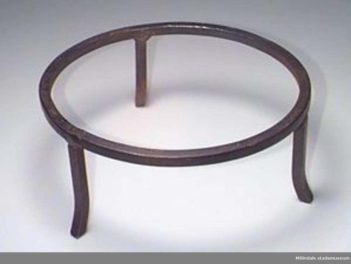 Av fyrkantig järnten. De tre benen har svetsats fast på en ring.Trefoten nytillverkad av en gammal man för brukaren. Funktion: För att kunna ställa grytor och pannor över öppen eld eller öppen härd, sattes en gångställning (en grytfot) över elden. Grytan eller pannan ställdes på denna ställning.