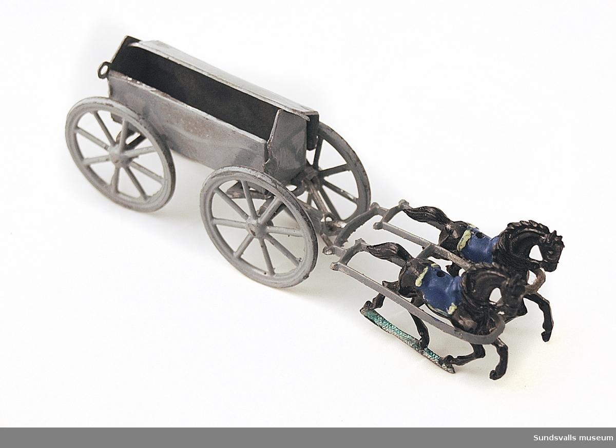 Tennleksak, ammunitionsvagn med förpackning. Löstagbart lock i pappkartong märkt 'Ammunitionsvagn'.