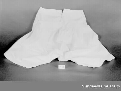 Benkläder i vitt bomullstyg med knäppning mitt fram och i sidorna med tygklädda knappar. Midjan har två lager tyg. Bakstycket fortsätter i två breda bitar runt midjan. Benen avslutas med uddkant broderad med langettsöm. Vitt monogram på vänster framsida.