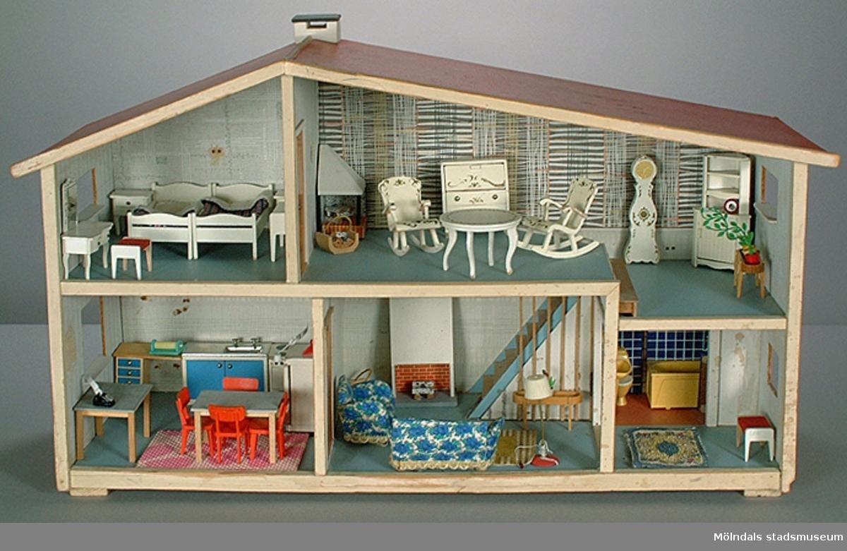 """Matta, mönstrad i olika färger. Hör till dockskåp MM03740:1.Givaren hade dockskåpet tillsammans med sin tvillingsyster Birgitta (Bibi). Det var en gåva från mormor, och ingen av kamraterna hade ett så fint dockskåp. Givaren berättar att hon lekte med dockor """"långt efter att andra slutat"""".Familjen bodde på Lekskolegatan i Mölndal. Mamman var hemmafru tills givaren var 17 år. Pappan var byggnads-ingenjör."""