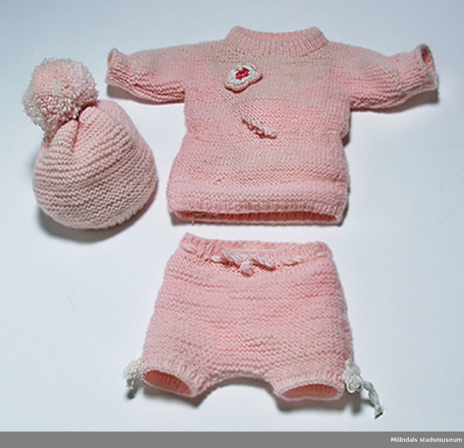 Olle till docka, stickad i ljusrosa garn och med en virkad blomma på bröstet. Samhör med mössa MM03870:1 och byxa MM03870:3.