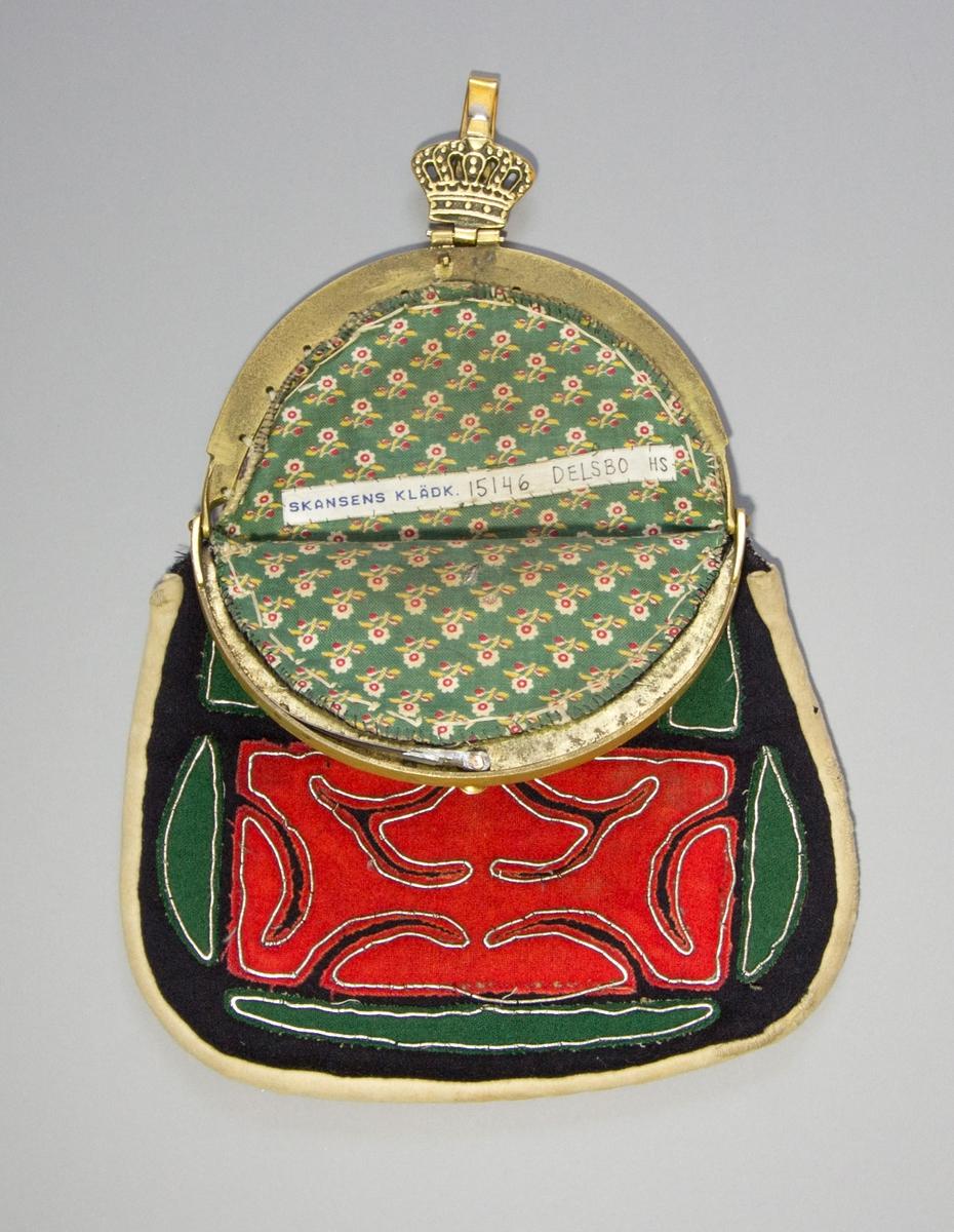 Kjolsäck till dräkt för kvinna från Delsbo socken, Hälsingland. Model med bygel. Framstycke av svart ylletyg, kläde, med applikationer av rött och grönt kläde. Regelbundet utklippt mönster, accentuerat av tenntrådsbroderiet, som använts för att sy fast applikationen med. Kantad med remsa av ljust sämskskinn. Bygel med snäpplås, gjuten av mässing, gjuten dekor på främre bygeldelen. Gångjärnsmekanism upptill med gjuten krona och hake. Baksida av ljust sämskskinn. Foder av bomullstyg med tryckt mönster, småblommigt på grön botten.