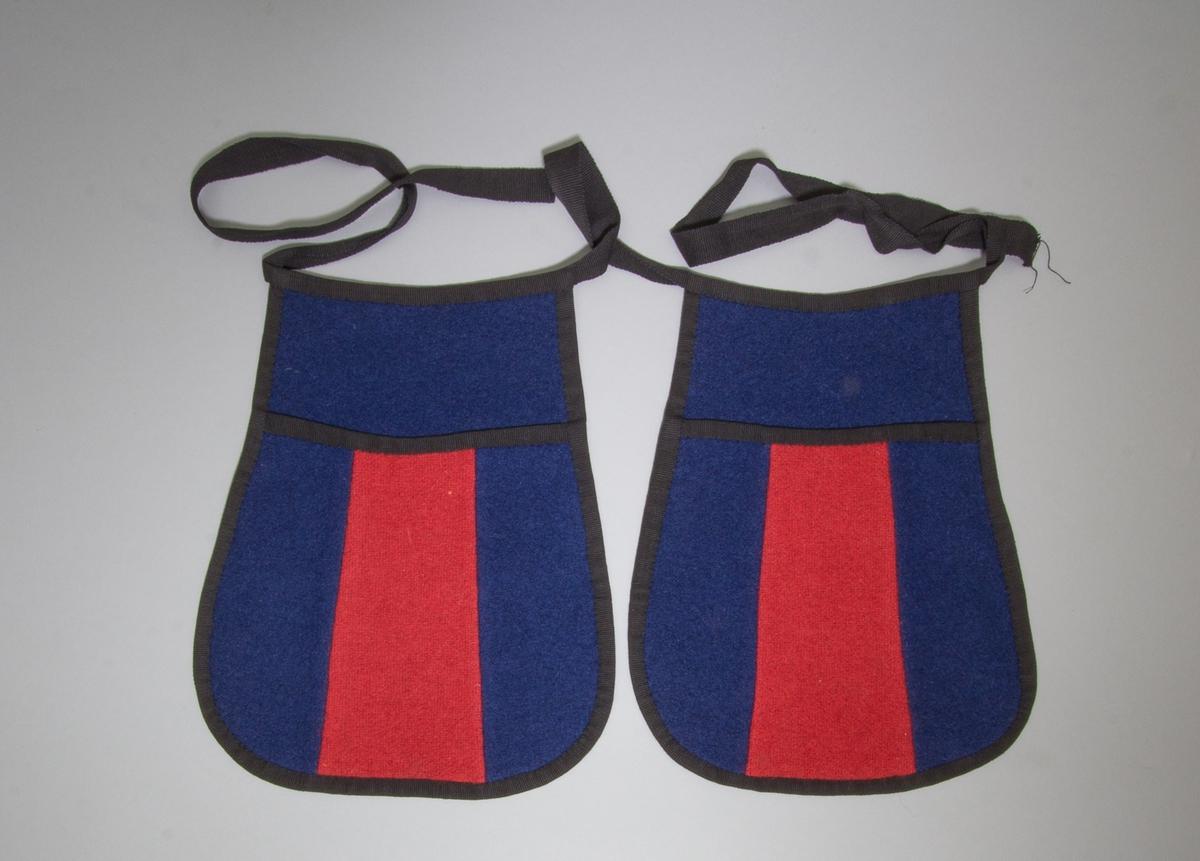Kjolsäck till dräkt för kvinna från Östervallskogs socken, Värmland. Modell med avskuret framstycke. Tillverkad av två ylletyger, troligen handvävda i tuskaft och sedan stampade, ett rött och ett mörkblått. Framstycket sytt av tre delar, med rött tyg i mitten. Ofodrad. Bakstycke av det blå tyget. Kantad runtom med svarta bomullsband, troligen handvävda i tuskaft. Samma band har använts till midjeband, med två kjolväskor påmonterade, en på var sida.