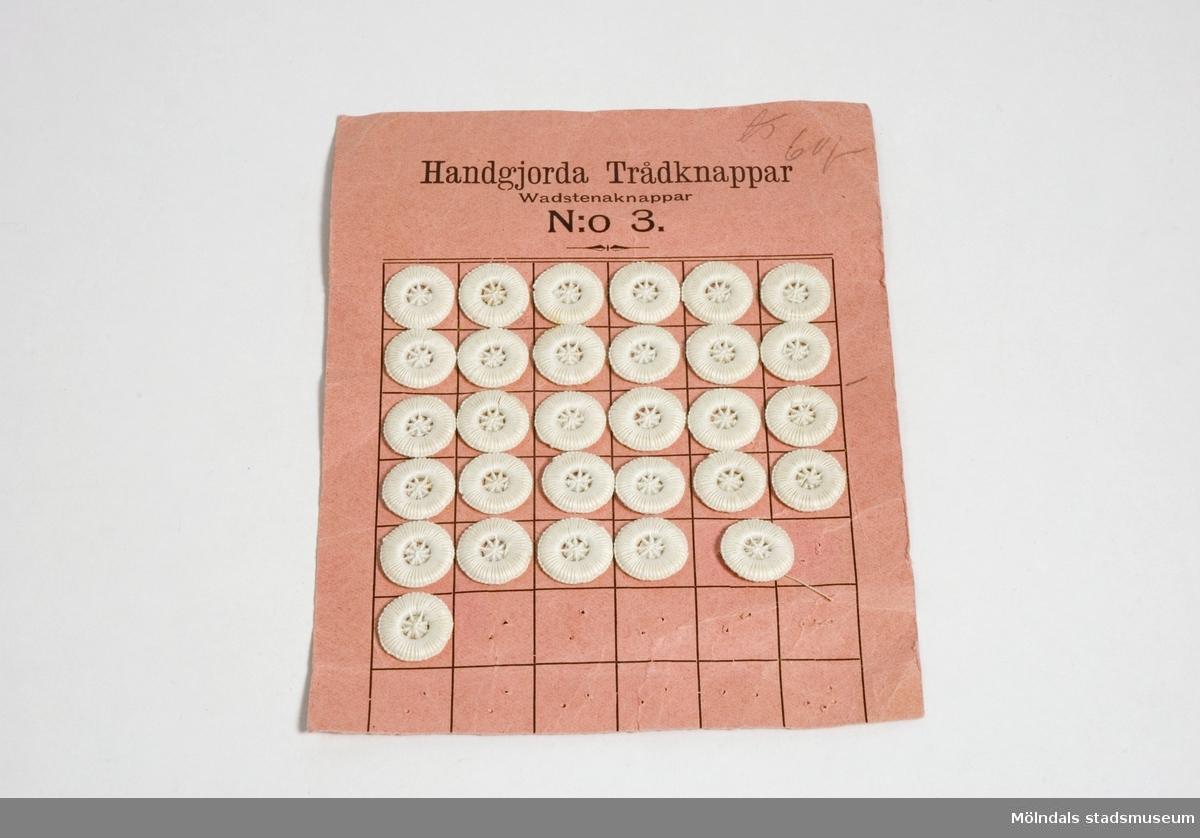 Vita, handgjorda trådknappar, s.k. Wadstena-knappar, uppsatta på en papperskarta. 30 st.
