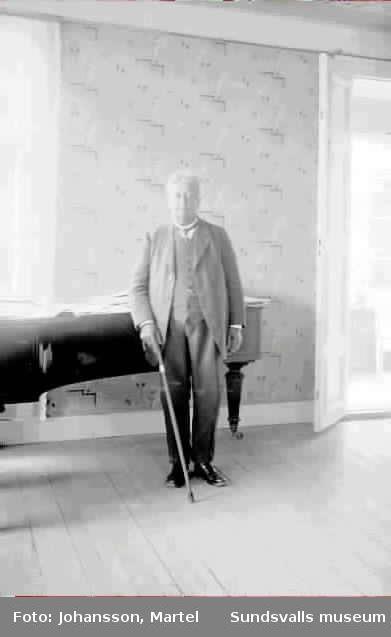 Porträtt på en man som står framför ev ett piano.