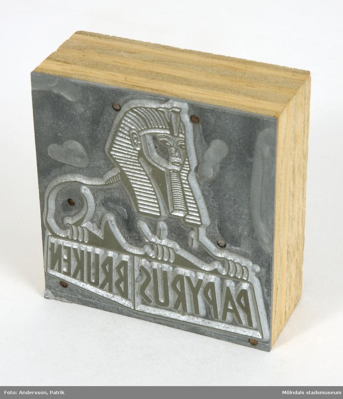"""Trycktyp som använts för tryck på papper på Papyrus. Typen är av trä med tryckplatta i metall. Motivet är Papyrus logotyp, sfinx på fundament, där det står """"Papyrusbruken"""". Troligen från 1970- eller 1980-talet."""