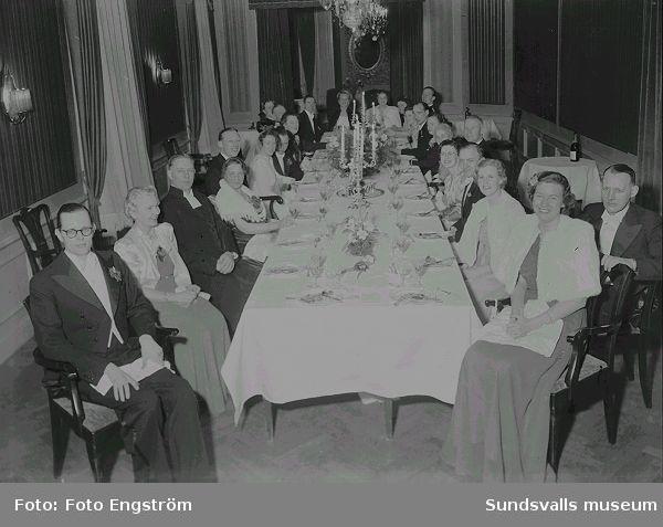 Porträtt, festlokal med festklädda män och kvinnor, vid dukat bord.