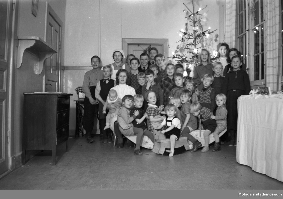 """Mölndals barnhem (f. d. Holtermanska) Rudbergsgatan. Gruppfoto av barn och personal framför julgran. Direktören Martin Holterman i Ostindiska kompaniet ägde Åby gård. 1782 skänkte han 3000 daler silvermynt till Fässbergs församling + ett nybyggt skolhus och trädgård på gårdens ägor vid Åby by. I skolan skulle 10 fattiga barn undervisas i """"kristendom, skrivande och något räknande. Holtermans skola fanns kvar till 1875. Då hade donationens ändamål ändrats, och man byggde i stället ett barnhem kombinerat med småskola. 1914 brann barnhemmet och 1915 byggdes ett nytt barnhem på samma tomt. 1929 överlämnades barnhemmet till Mölndals stad."""