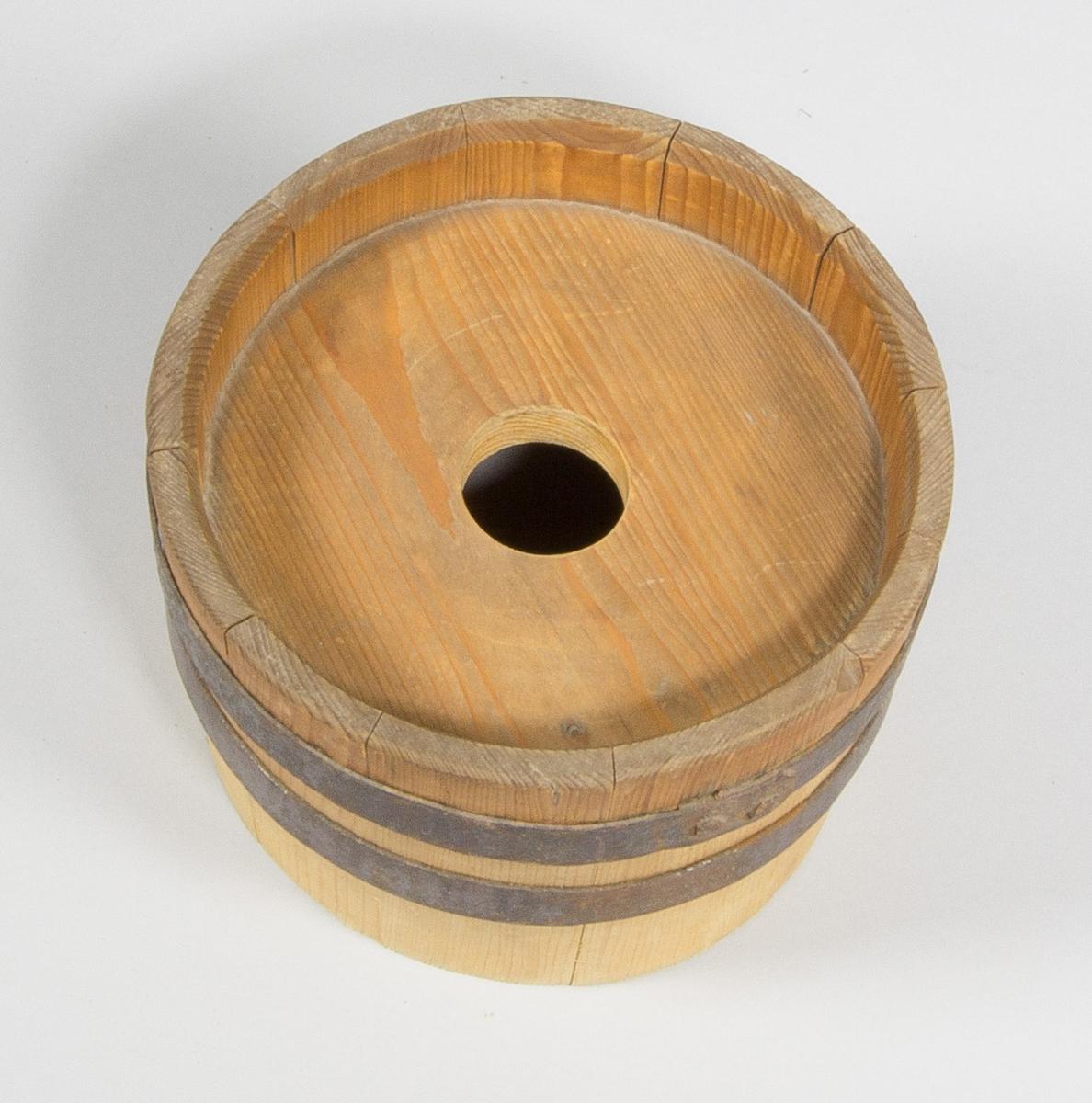 Lock till smörkärna, i trä. Laggade höga väggar med två järnband runt omkring. I mitten rund platta med hål för kärnstaven.