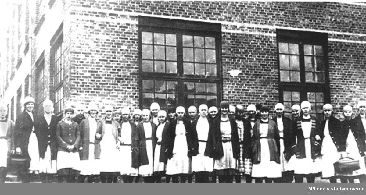 """Anderstorps fabriker i Lindome på 1930-talet. Spinneriarbeterskor framför Nya spinneriet. Nr 15 fr. vä. Ruth, nr 28 Olga, nr 29 och 30 systrarna Olsson från Dvärred 3:20.  """"Kvinnliga arbetare utanför spinneriet. Lägg märke till huvudbonaderna. Dessa utgjorde skyddsklädsel för att håret ej skulle fastna i maskinerna"""". (anteckningar av Harry Bergman)."""