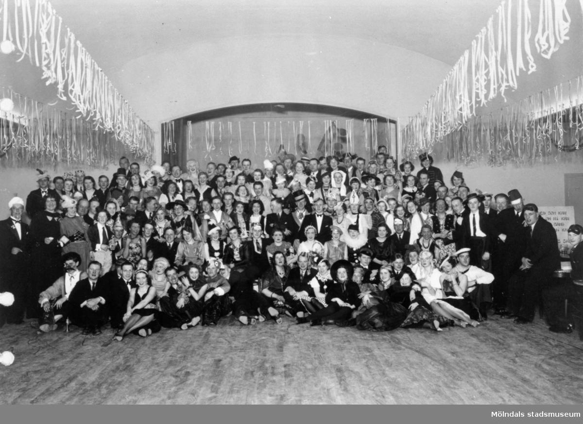 Maskerad på Gillet. Mölndals körsällskap sittande respektive stående framför scenen, mars 1938.