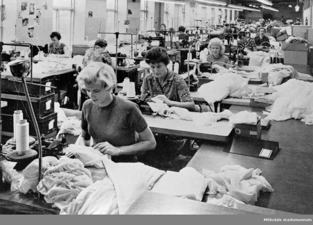 """Sömmerskor arbetar i sömnadssalen på fabriken Eiser, 1950. Eiser ingick i bolaget Sveriges Förenade Trikåfabriker Avd. G. Kallades Stora Götafors i folkmun.  Bilden är hämtad ur boken """"Garn och gagn - en krönika om trikå utgiven till hugfästandet av ett textilt halvsekeljubileum 1913-1963""""."""