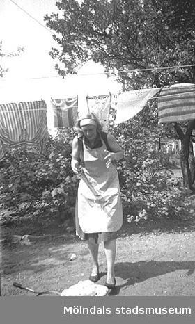 Givarens moster/fotografens syster, Ingrid Karlsson, hänger tvätt i Åbyområdet, 1955.