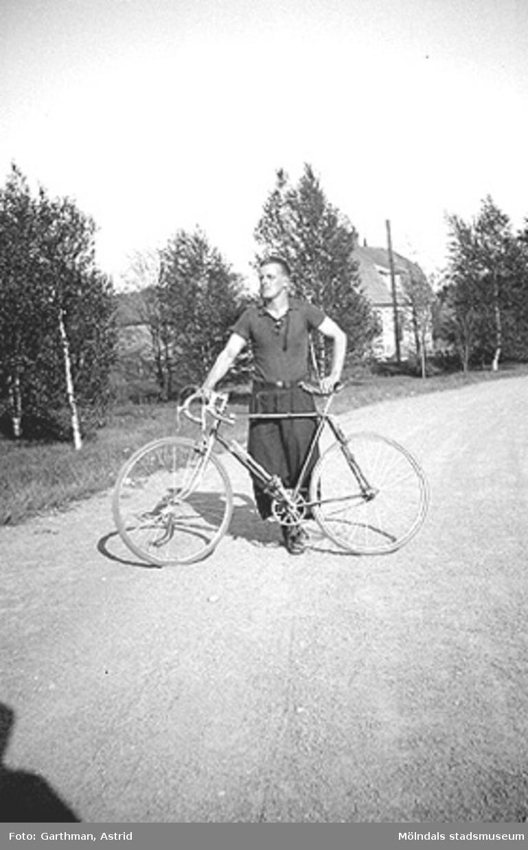 Helmer Garthman står på en grusväg bredvid sin cykel. Fjärås Bräcka, 1930-tal.