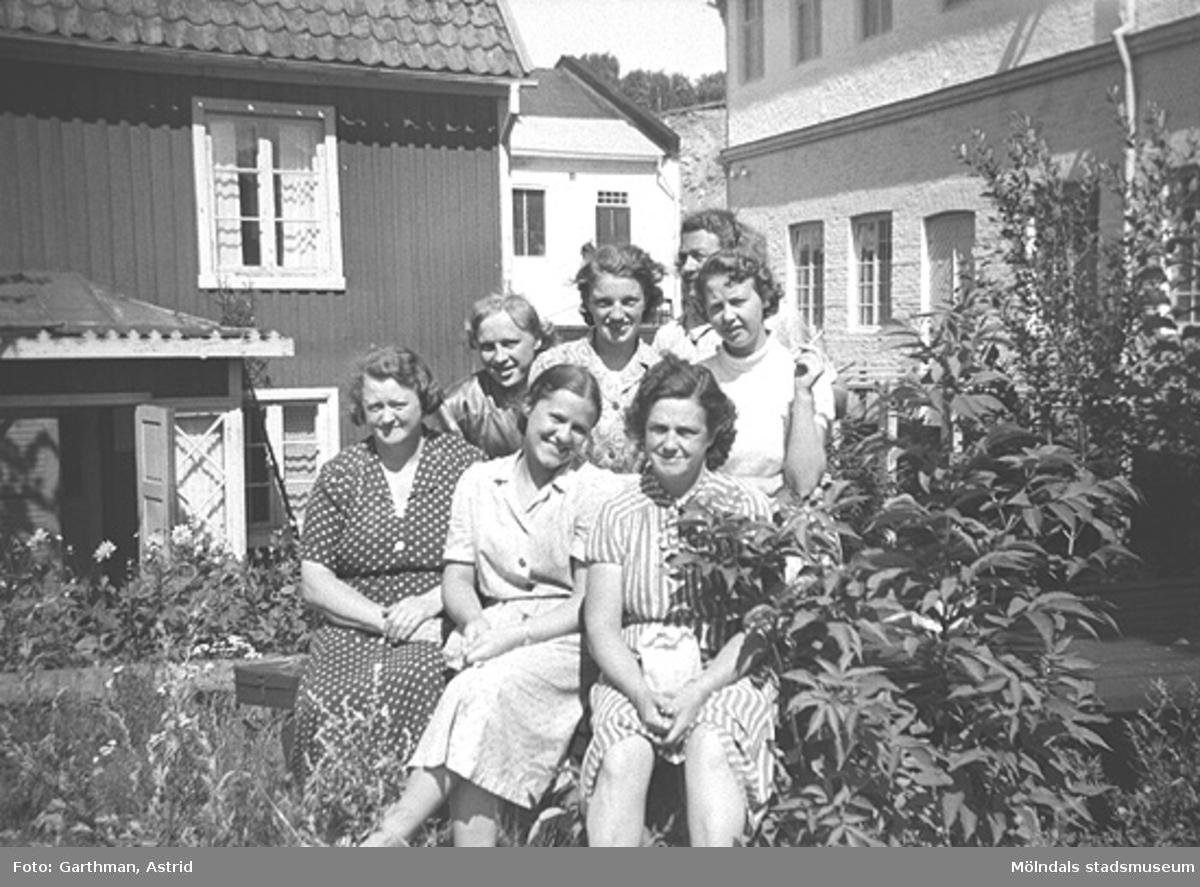 """Sju kvinnliga arbetskamrater (okända för givaren) står/sitter i gräset framför ett hus och en fabrik. De är från """"Lumpans"""" (Forsåkers fabriker), Kvarnfallet 31. Detta är öster om järnvägsvallen under 1950-talet."""