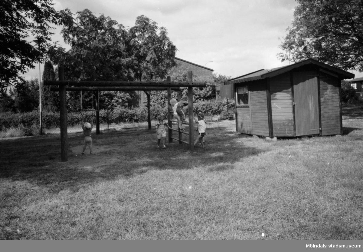 Flera barn som leker i en klätterställning på en gräsmatta utanför Katrinebergs daghem. Ett förråd står vid sidan om. 1992-93.