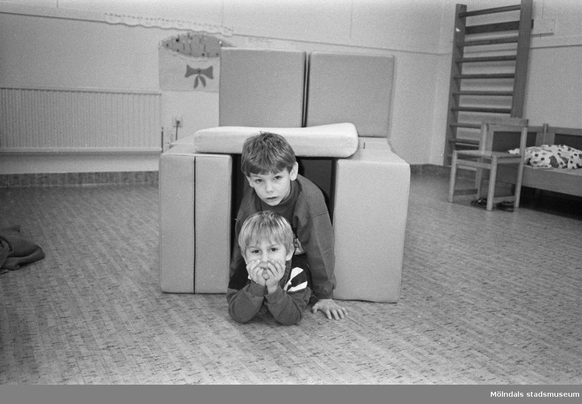 Två pojkar tittar fram från en egenbyggd koja. Den består av småkuddar som omringar dem på sidorna och ovanpå. I rummet kan man se en vägghängd ribbstol, en liten säng och en barnstol. På golvet ligger en kork-liknande linoleum-matta.