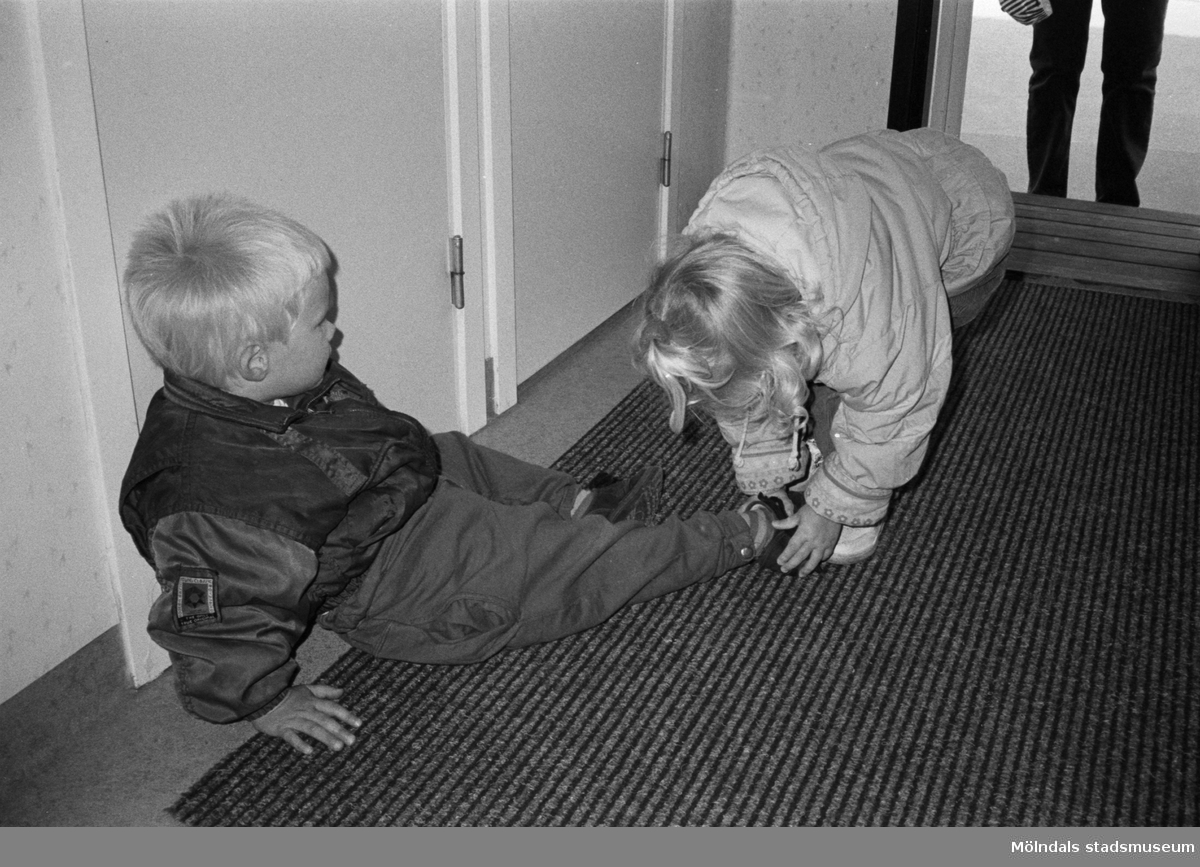 Robin, som sitter på innegolvet, får hjälp med sina skor av ett annat dagisbarn. Hoppetossan, Katrinebergs daghem, 1992.