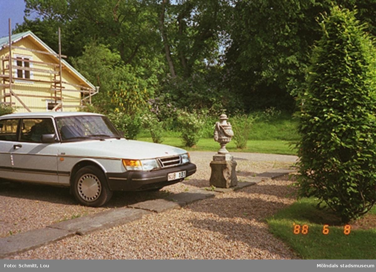 En vit Saab står parkerad framför en blomsterurna vid Gunnebo slott.