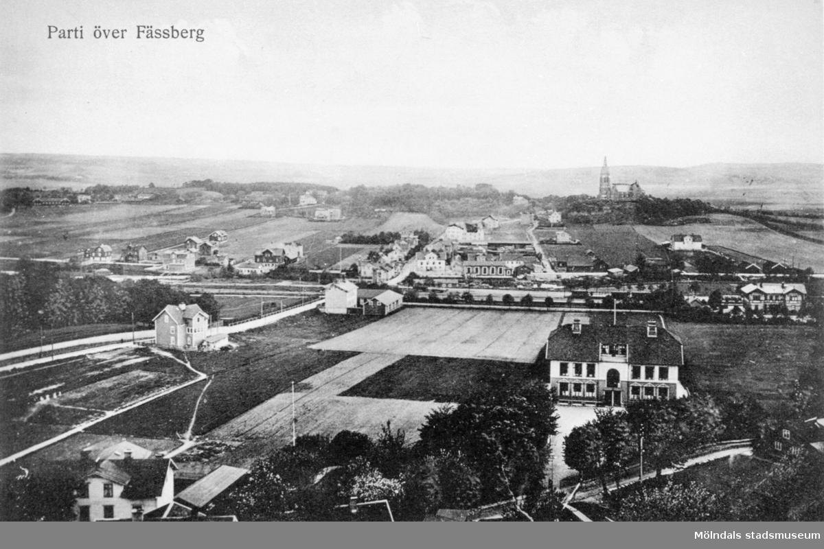 """Vykort """"Parti över Fässberg"""" med utsikt från området Trädgården mot Mölndals bro i väster. Man ser delar av Kvarnbygatan, Göteborgsvägen, Frölundagatan och Bergmansgatan. I förgrunden ligger Trädgårdsskolan. Bilden är tagen tidigast 1907, eftersom spårvagnshallarna är med, men inte långt efter, ty bebyggelsen är ännu gles."""