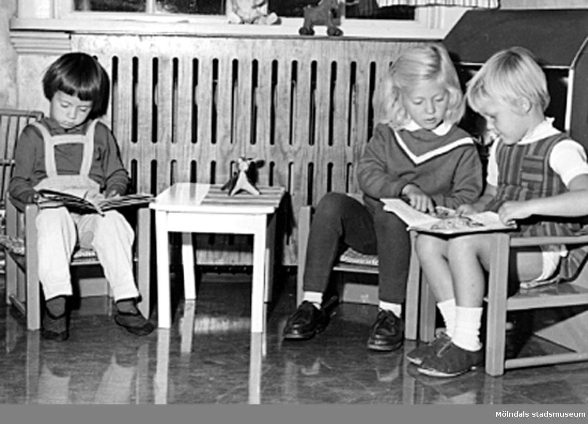 Tre flickor sitter vid ett litet bord och läser. Holtermanska daghemmet 1953.