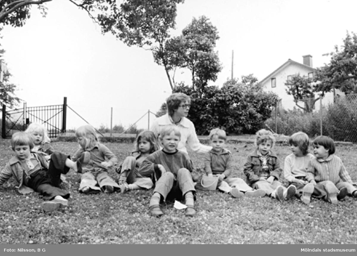 Några barn och en fröken sitter i gräset. Holtermanska daghemmet 1973.