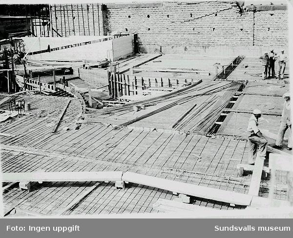 Armeringsarbete vid byggandet av Philipsons bilaffär, Norra Järnvägsgatan 8, 1939-07-12. Bland betongarbetarna finns bl.a. Erik Edblad (f. 1908). Han var verksam som anläggnings- och betongarbetare och senare som yrkeslärare i betong-och hållfasthetslära.