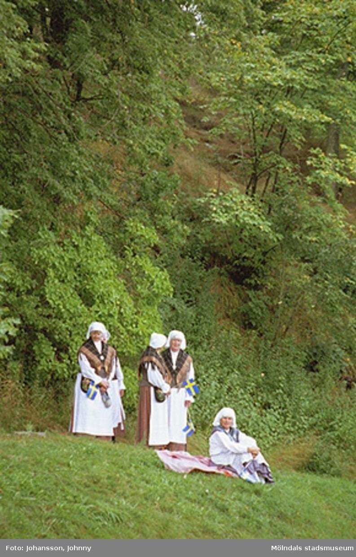 Fyra kvinnor iklädda Mölndalsdräkt, står i grönskan och inväntar kungabesök. Längst till höger Maria Gahrn.