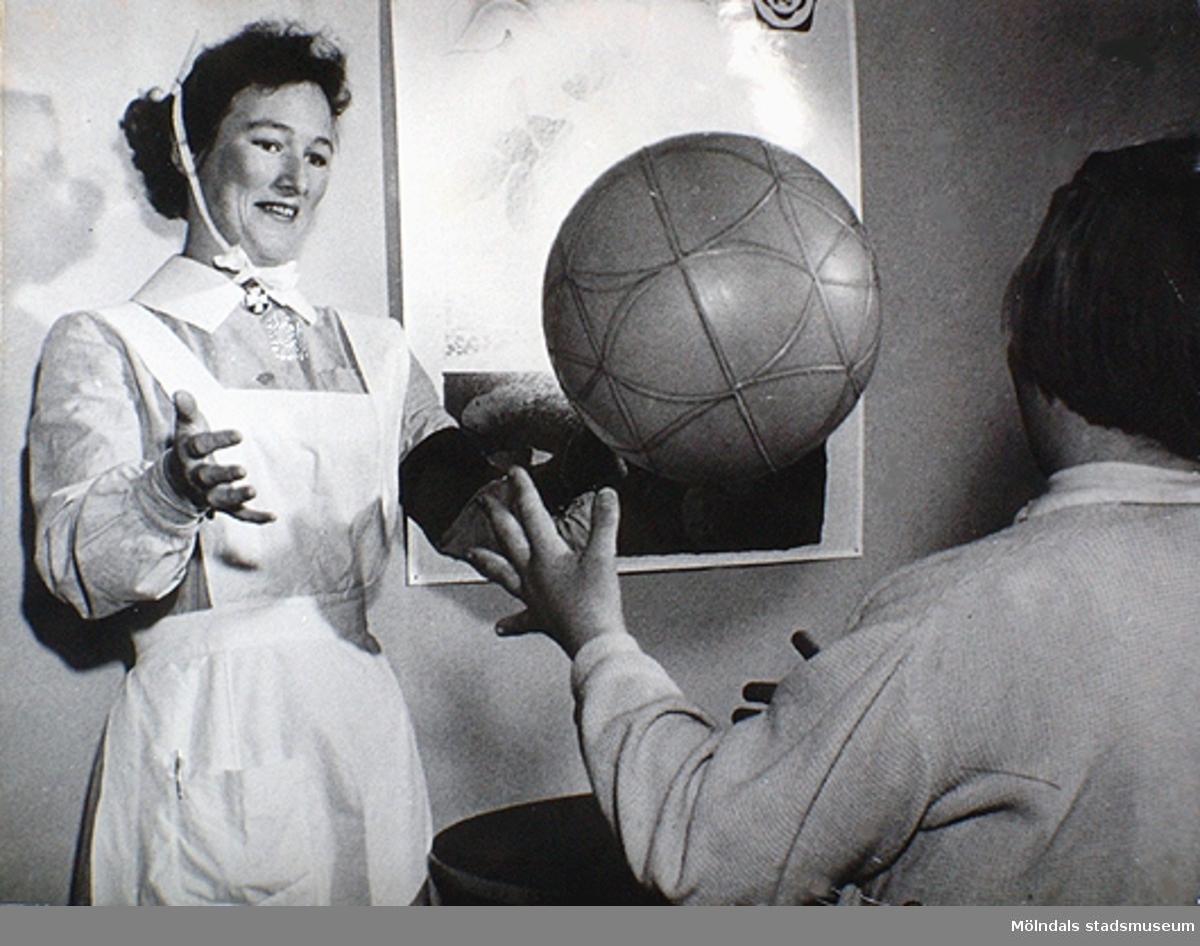 En sjuksyster som kastar boll tillsammans med ett barn. Under 1950-talet kom allt fler specialister, t ex sjukgymnaster. Okända namn och årtal.