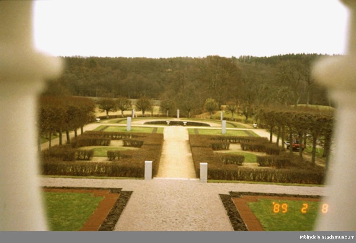 Vy på parken och skogen åt söder, fotograferad mellan två stolpar som tillhör slottstrappan. Detta för att få djup i bilden.