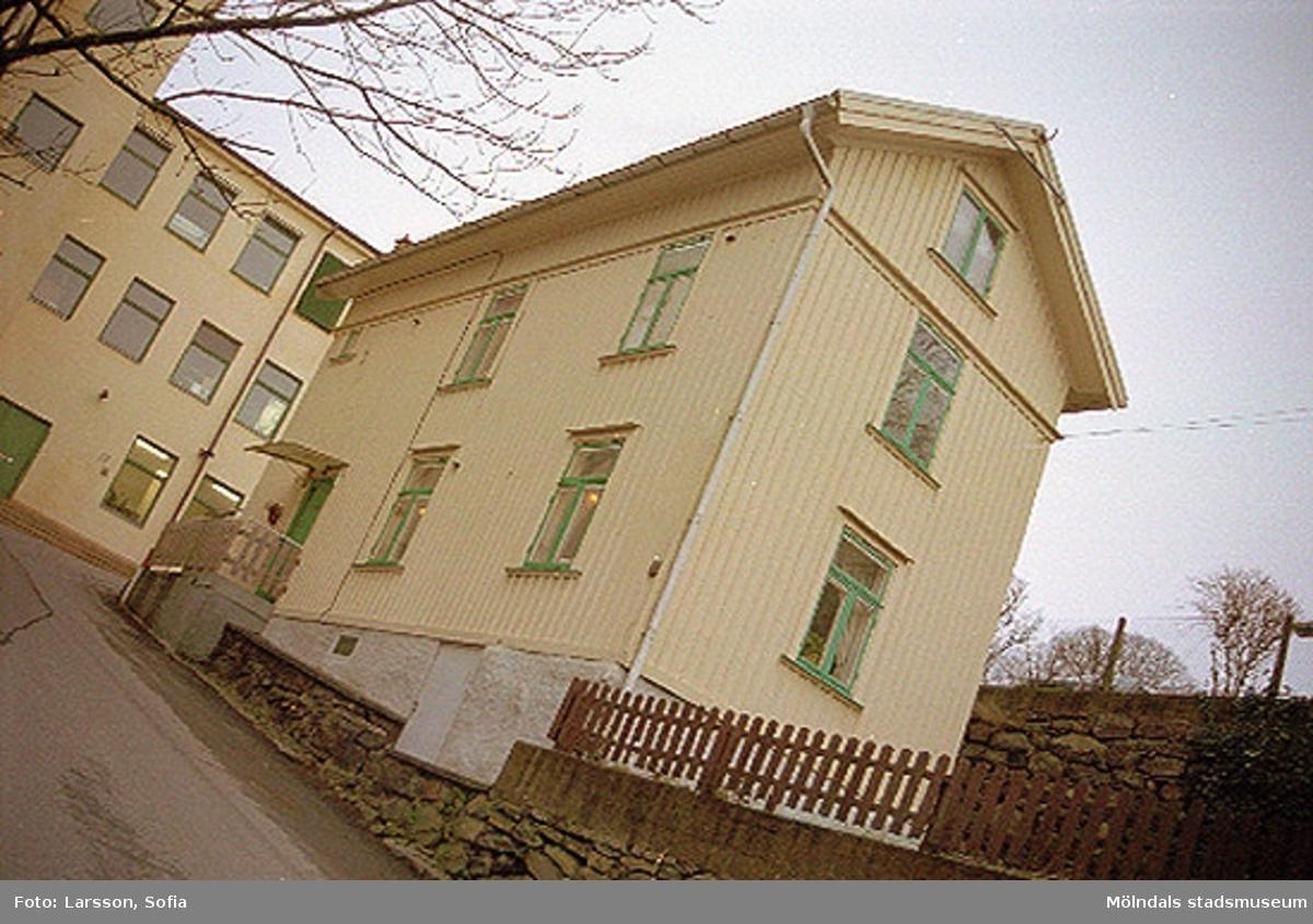 Götaforsliden 18, den före detta kvarngården med dess murar och staket. I bakgrunden till vänster ses det tidigare Ahlafors textilindustri. Det byggdes år 1856 och har sedan byggts om flera gånger. Senast var på 1940-talet.