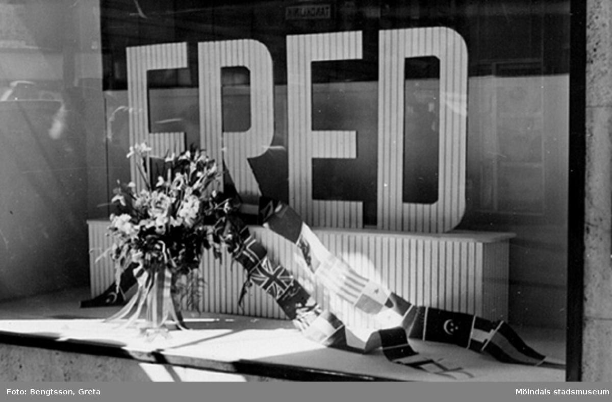 Vi firar FREDEN, åker in till Göteborg och lunchar på Gillblads! 1943-1946.Orden FRED och blomsteruppsättning i skyltfönster (på Gillblads?).Laboranter från SOAB-Svenska Oljeslageri AB, Kvarnbygatan, Mölndal.