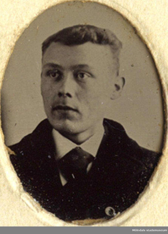 Fotot är ett bystporträtt av en man.
