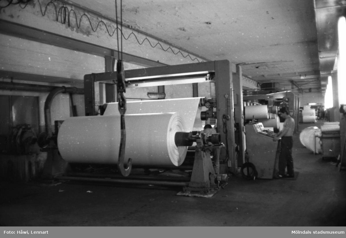 Man i arbete vid rullmaskin 5, byggnad 10 på Papyrus i Mölndal, hösten 1970. Mannen på bilden arbetar som rullare och sköter maskinen med hjälp av manöverbord.