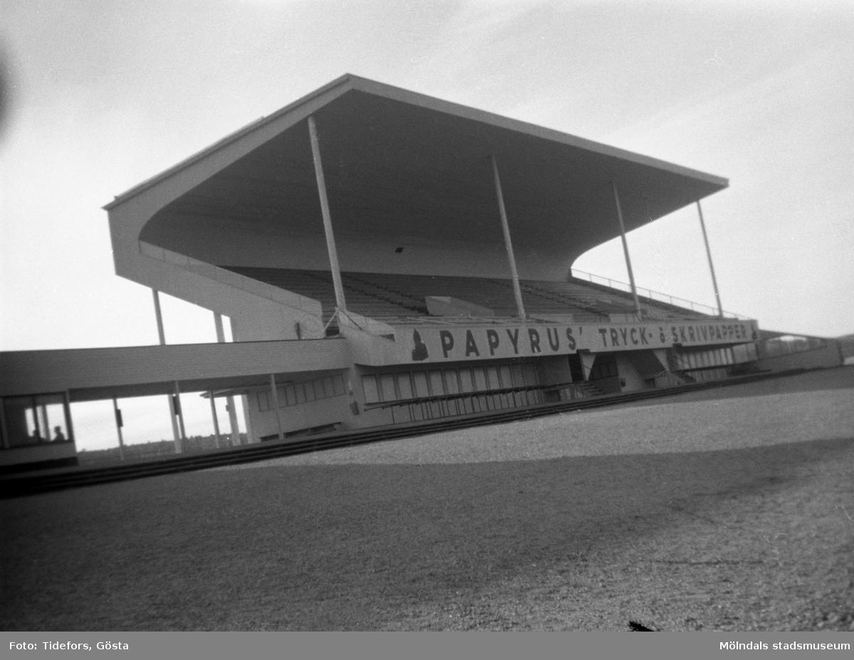 """Idrottsplats i Mölndal, 1943.På läktaren finns reklam för: """"PAPYRUS' TRYCK å SKRIVPAPPER""""."""