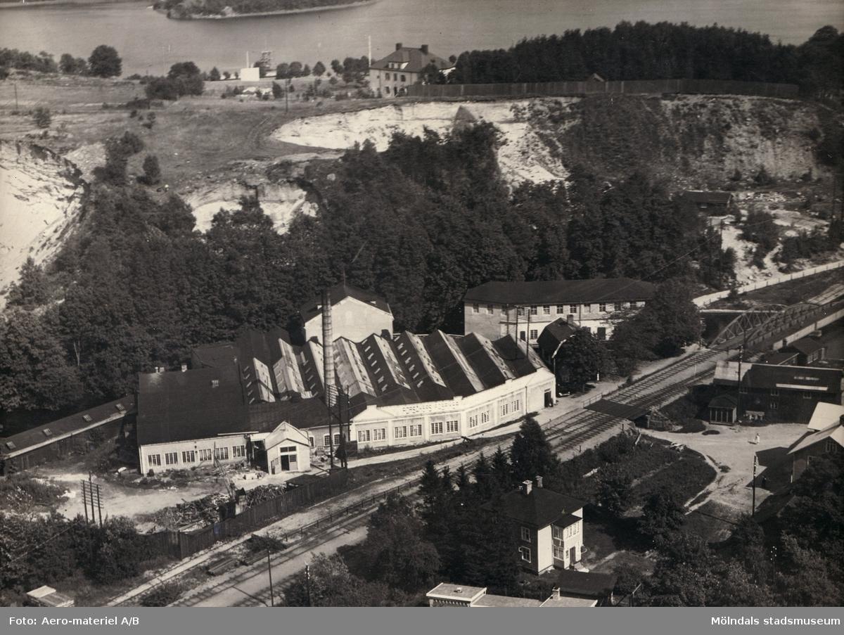 Inramat flygfoto över Forsåkers fabriker vid Grevedämmet i Mölndal. I bakgrunden ses Stensjön och Stensjöhill. Fabriksbyggnaden kallades även för Bettyholm och Carlsfors fabrik.