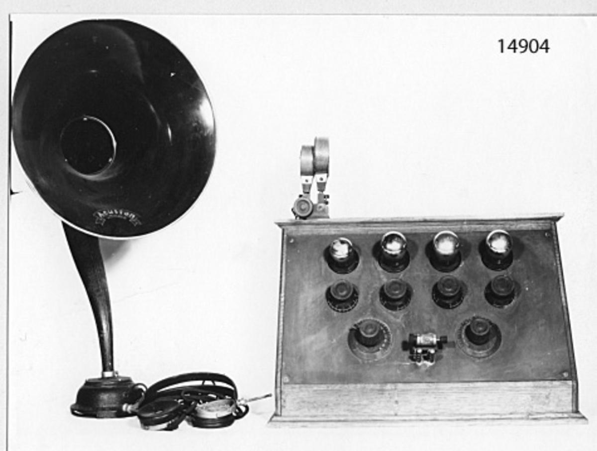 Mottagaren inbyggd i en låda av ekträ, som är snedskuren med lock på baksidan. På framsidan, som är av bakelit, fyra rör, sex rattar med skalor samt detektor i glashölje. På översidan två spolar, en fast och en vridbar.