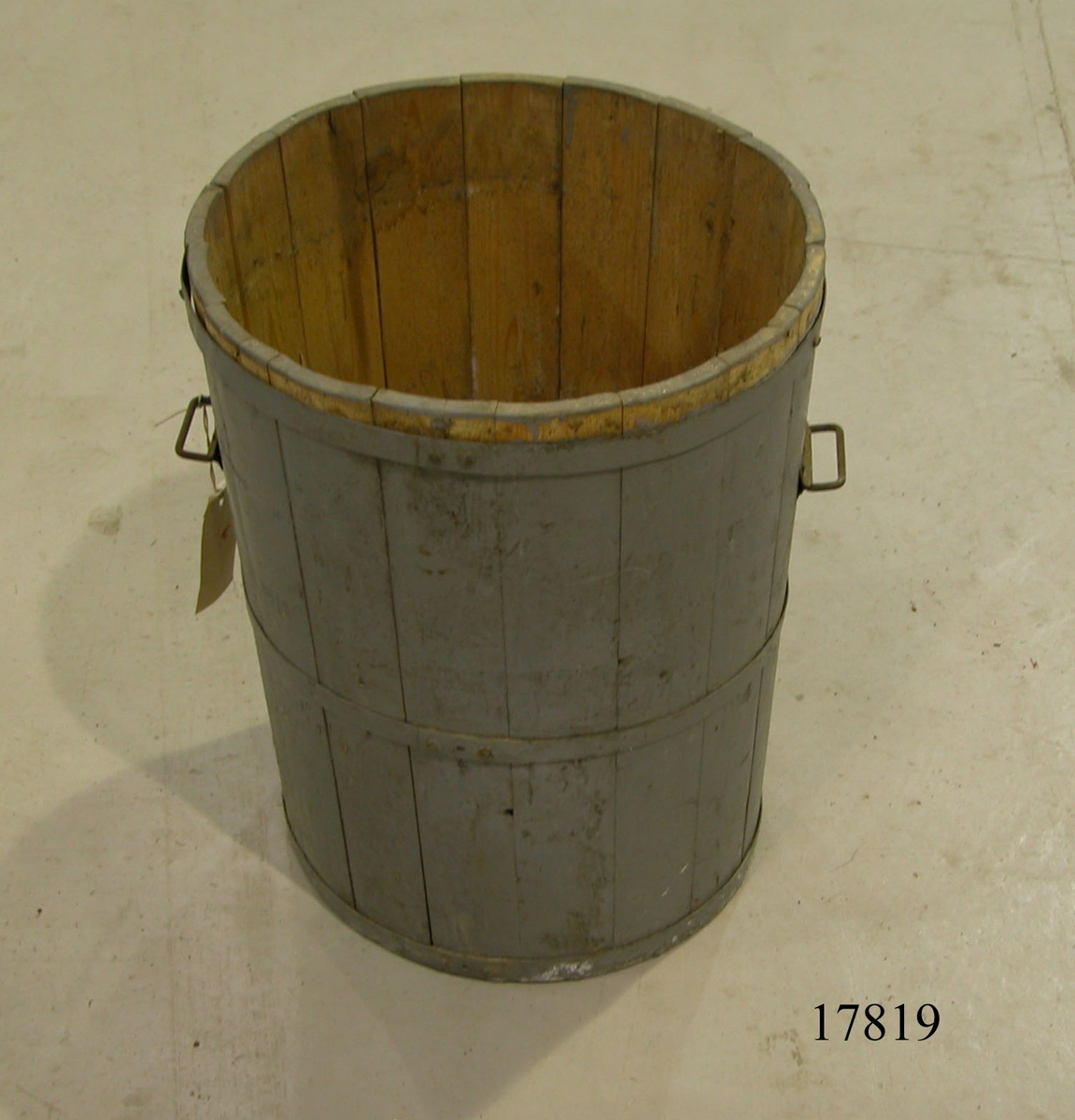 Tunna av fur, cylinderformad. Järnband nitat till botten samt två band runt tunnan. Allt målat i grått. Två svartmålade bygelhandtag, fästade till bleck.