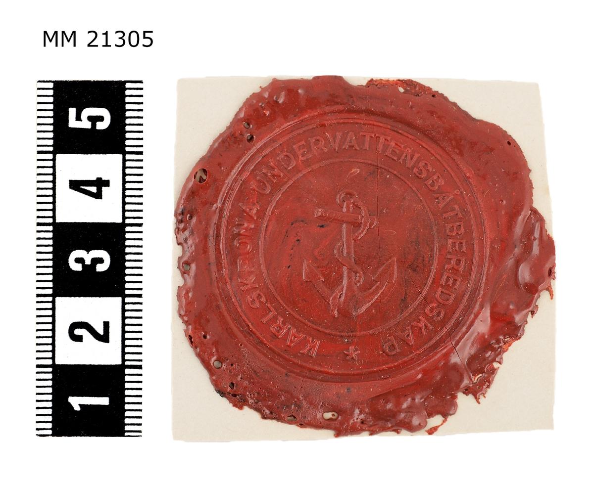 """Sigillavtryck av rött lack på papper. I mitten krönt sköld med tre kronor omgivet av serafimerkedja. Längs kanten text: """"Karlskrona Undervattensbåtberedskap""""."""
