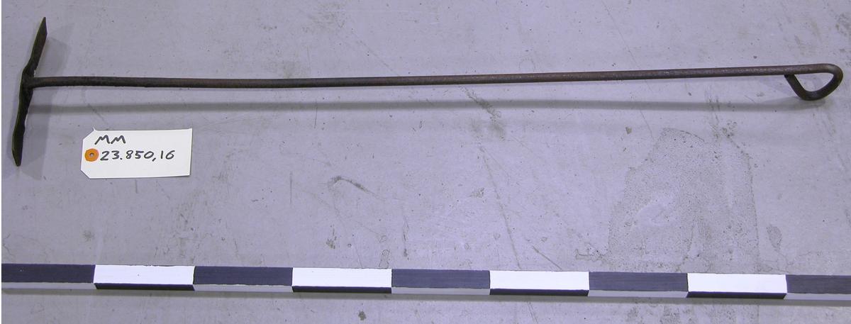 Svart skrapa i järn för bruk vid smedja. Försedd med en liten kringla i skaftets ände. Föremålet har anlänt till Marinmuseum från Verkstadsskolan den 7:e mars 1988.