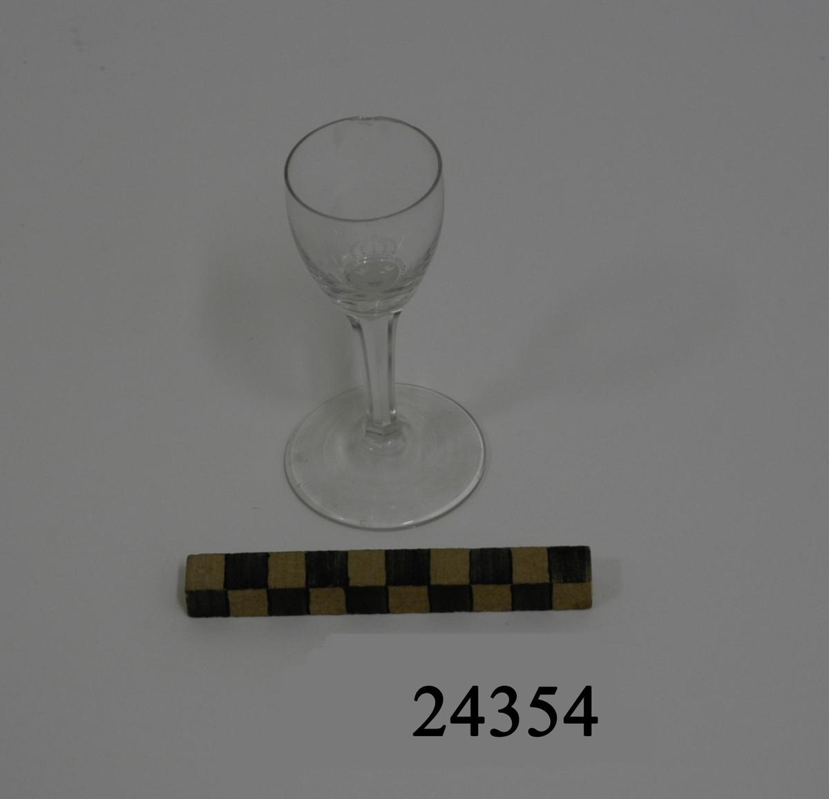 Sherryglas med liten välvd kupa. Smalt fasettslipat ben. Rund plan fot. På kupan inetsat, lilla riksvapnet omgivet av serafimerorden.